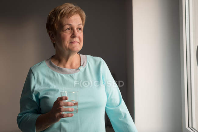 Thoughtful senior woman having glass of water at home — Stock Photo