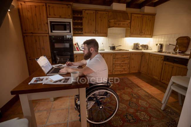 Використання ноутбука на дому інвалідів юнак — стокове фото