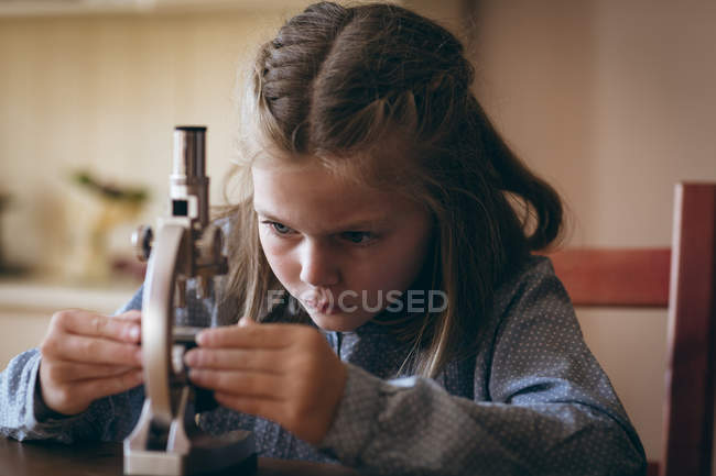 Girl experimenting with microscope at home — Stock Photo