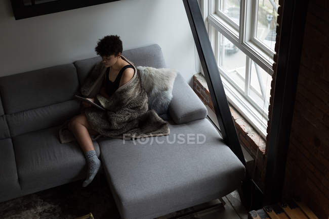 High angle view of beautiful woman using digital tablet while relaxing on sofa — Stock Photo