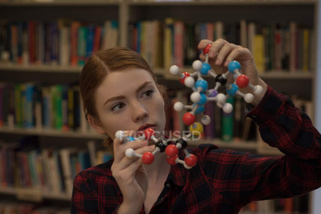 Young woman analyzing a molecule model in the library — Stock Photo