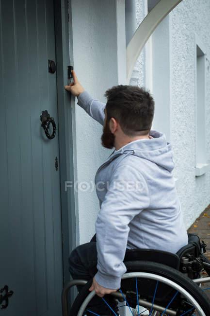 Homem deficiente tocando a campainha da porta de sua casa — Fotografia de Stock
