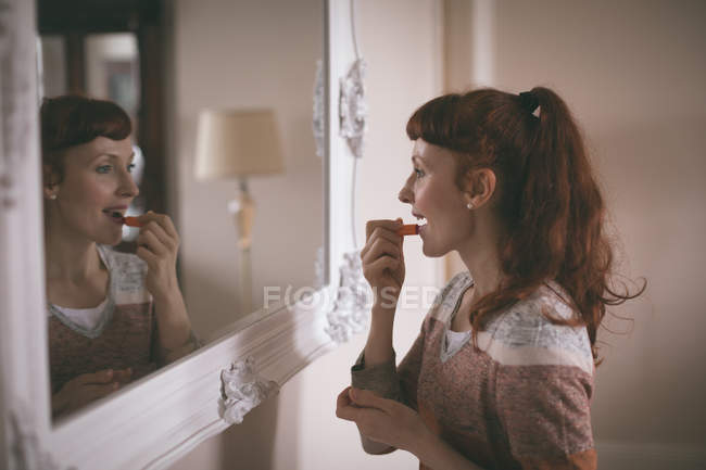 Woman applying lipstick in front of mirror at home — Stock Photo