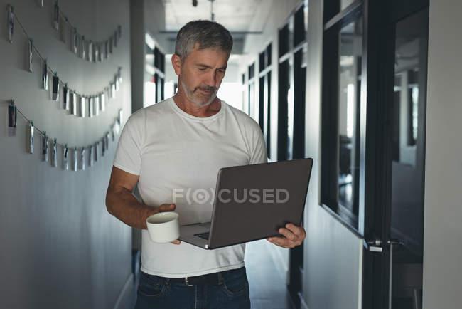 Empresário caminhando com laptop no escritório — Fotografia de Stock
