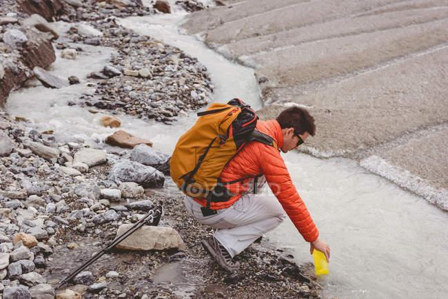 Вид сбоку мужской туристы розлива воды в бутылку из потока — стоковое фото