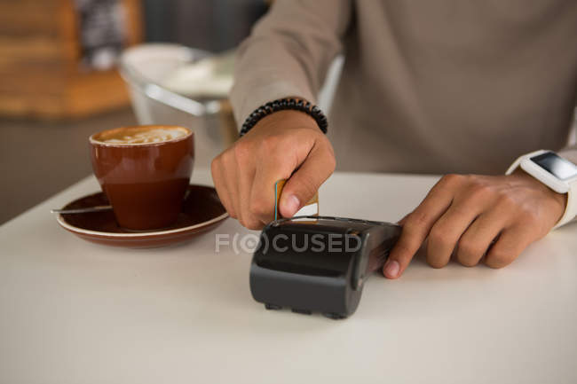 Man making payment through debit card in cafeteria — Stock Photo