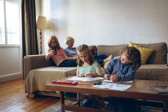 Sisters doing their homework in living room at home — Stock Photo