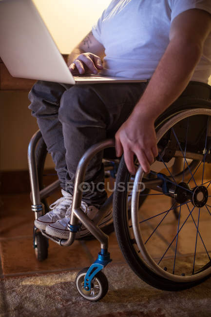 Low section of disabled man using laptop at home — Stock Photo
