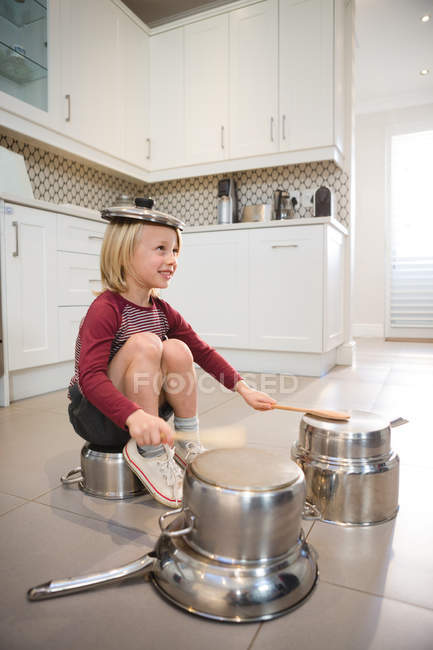 Boy playing with utensils in kitchen at home — Stock Photo