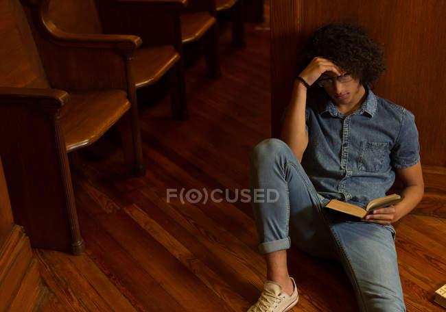 Giovane che legge un libro in biblioteca — Foto stock