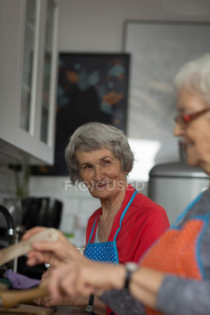 Senior friends interacting while cooking food in kitchen at home — Stock Photo