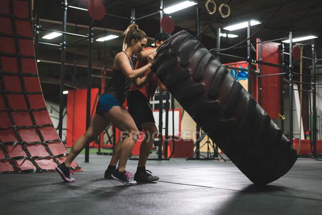 Мускулистая пара перевернула тяжелое колесо в спортзале — стоковое фото