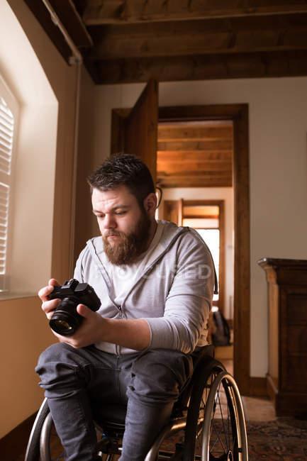 Disabled man looking at photos in camera at home — Stock Photo