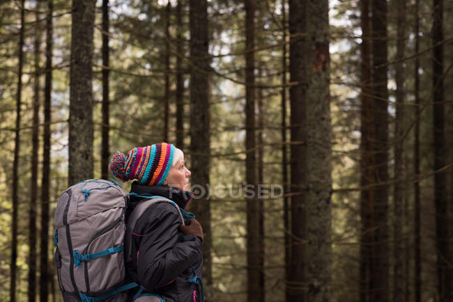 Pensativa mujer mayor de pie con mochila en el bosque - foto de stock