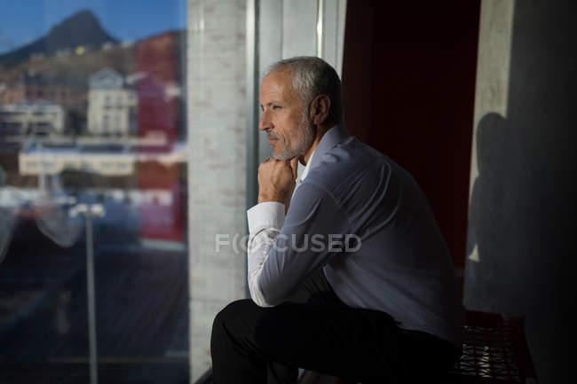 Задумчивый бизнесмен смотрит в окно гостиничного номера — стоковое фото