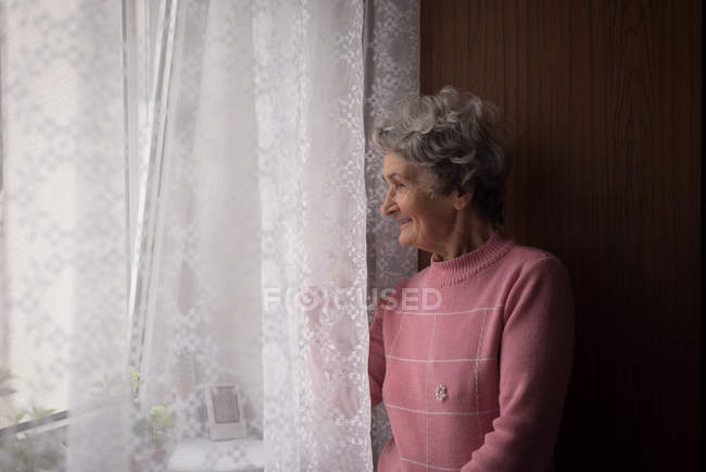 Senior woman standing near window at home — Stock Photo