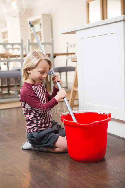 Boy holding floor mop with bucket at home — Stock Photo