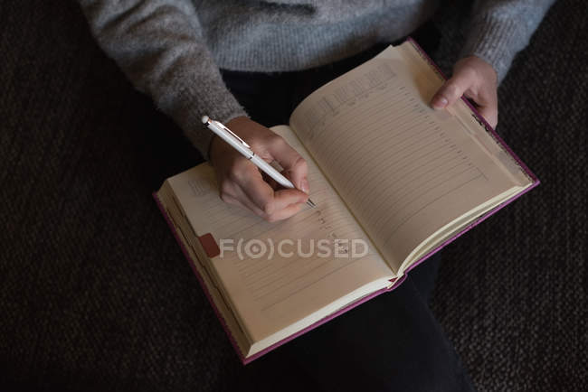 Woman writing note on diary in living room at home — Stock Photo