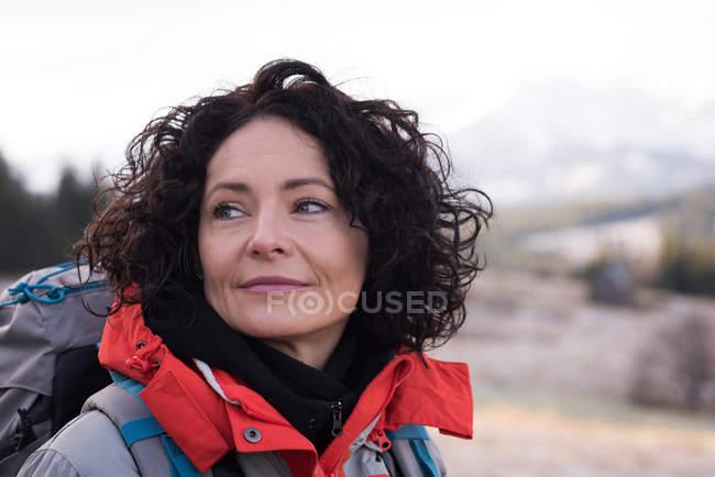 Задумчивая женщина, стоящая с рюкзаком зимой — стоковое фото