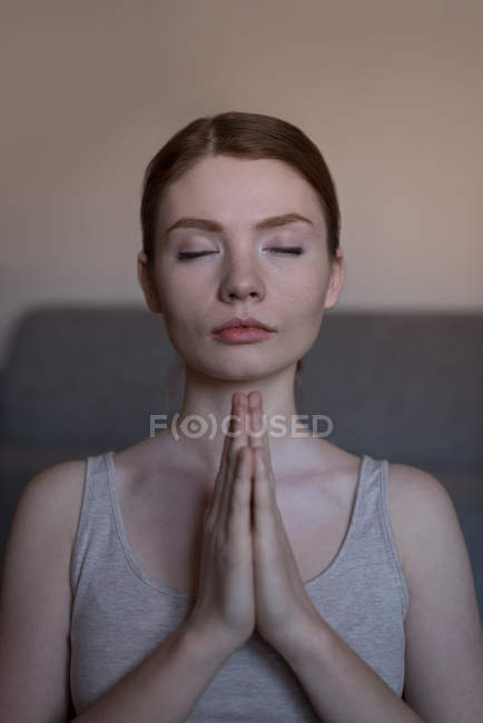 Close-up of young woman meditating with joined hands in living room — Stock Photo