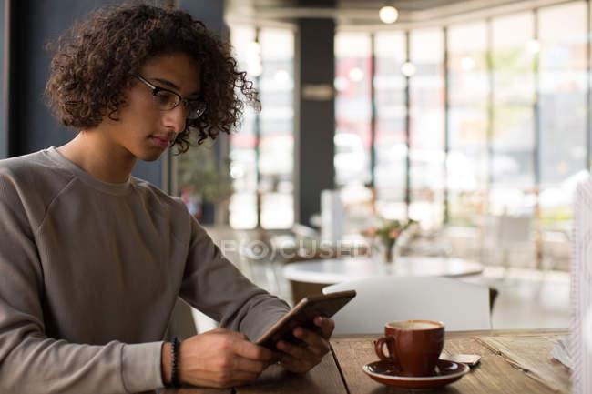 Junger Mann benutzt digitales Tablet in Cafeteria — Stockfoto