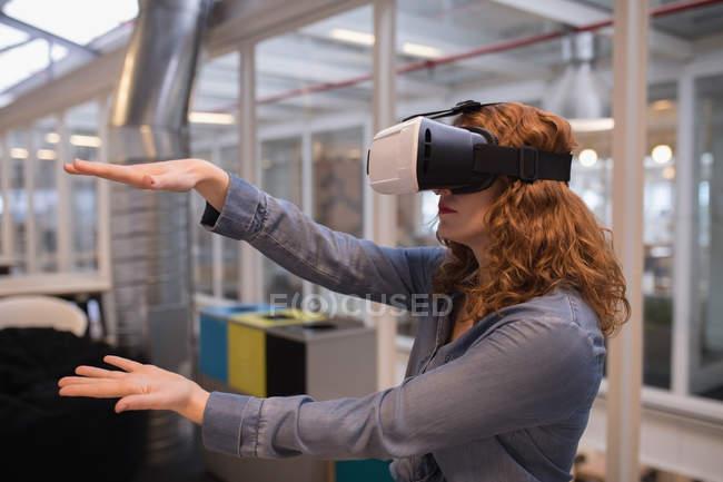 Esecutivo femminile utilizzando cuffie realtà virtuale in ufficio — Foto stock