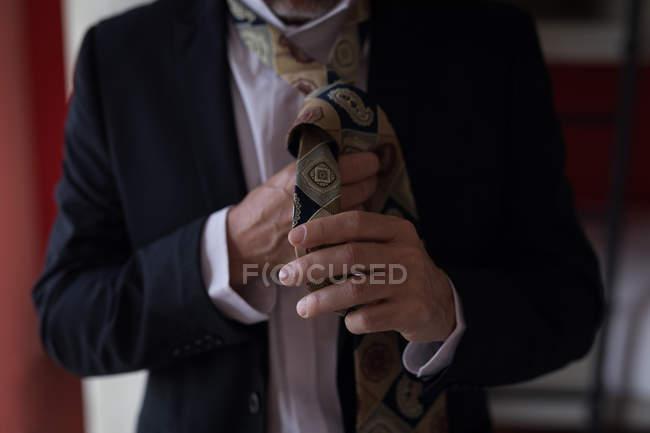 Gros plan d'homme d'affaires liant sa cravate dans la chambre d'hôtel — Photo de stock