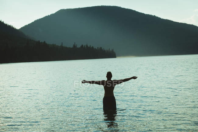 Vista traseira do homem de pé com os braços estendidos em um lago — Fotografia de Stock