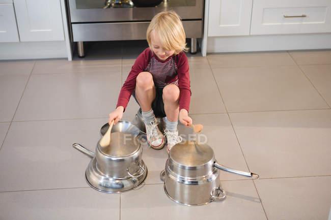 Мальчик играет с посудой на кухне дома — стоковое фото