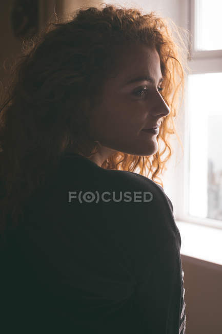 Close-up of thoughtful woman standing near window at home — Stock Photo