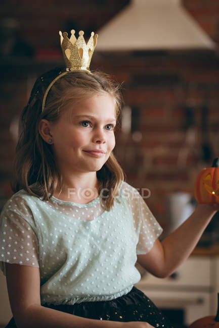 Cute girl with a crown holding pumpkin in kitchen at home — Stock Photo