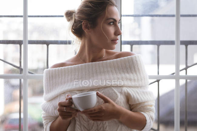 Thoughtful woman having green tea at home — Stock Photo
