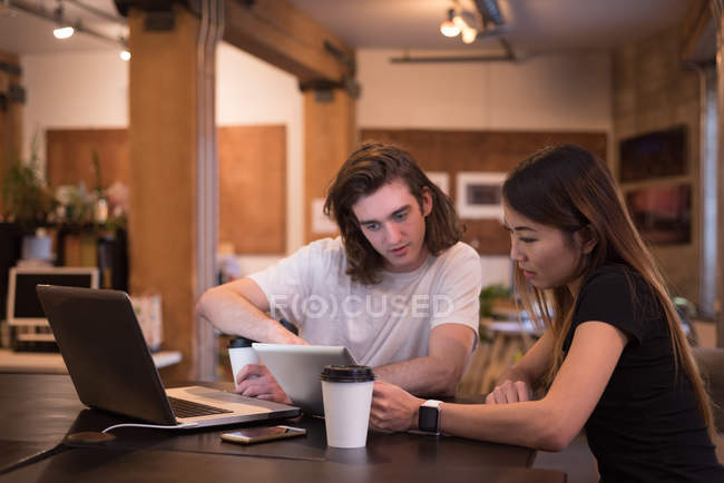 Business colleagues discussing over digital tablet at desk in office — Stock Photo