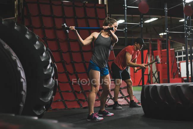 Мускулистая пара бьет по шине кувалдой в спортзале — стоковое фото
