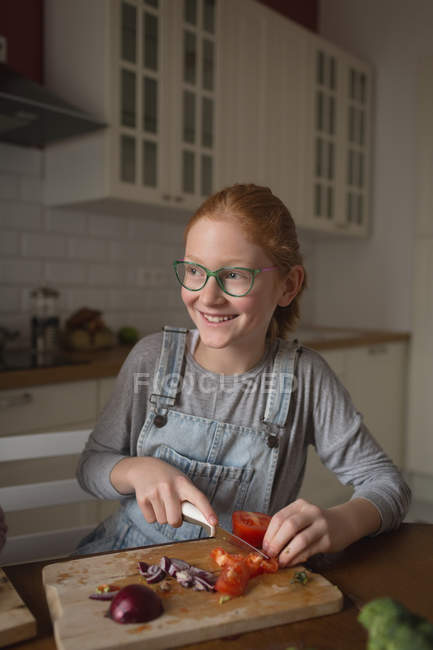Girl cutting vegetables in kitchen at home — Stock Photo