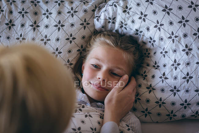 Mother wakes up her daughter on bed at home — Stock Photo