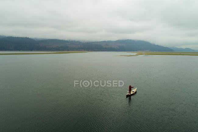 Maschio turista che viaggiano in barca canoa su un lago — Foto stock