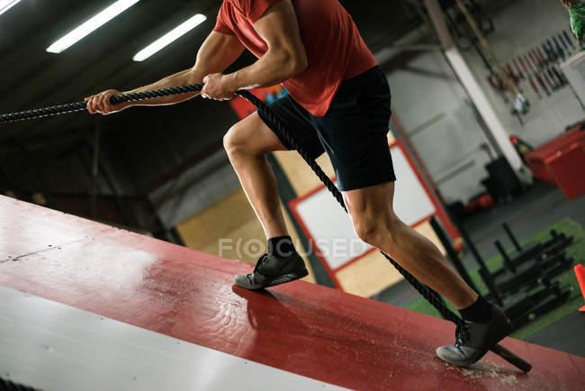Homme musclé escaladant un mur incliné avec une corde au gymnase — Photo de stock