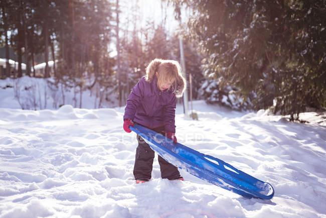 Linda chica con el trineo en nieve durante el invierno - foto de stock