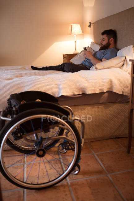 Disabled man using mobile phone in bedroom at home — Stock Photo