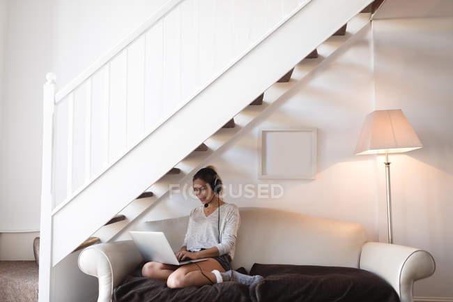 Frau benutzt Laptop mit Headset im heimischen Wohnzimmer — Stockfoto