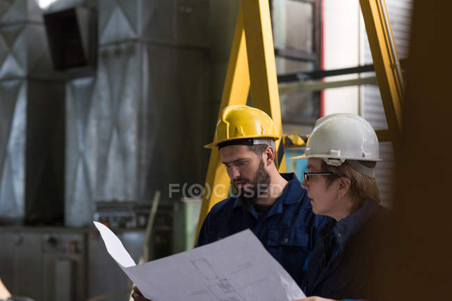 Technician discussing blueprint with his colleague in metal industry — Stock Photo