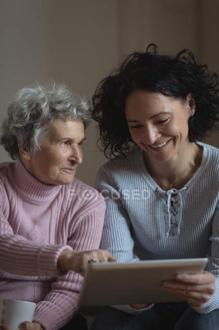 Mother and daughter using digital tablet in living room at home — Stock Photo