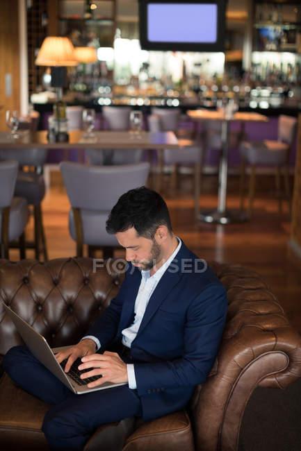 Empresario usando laptop en hotel - foto de stock