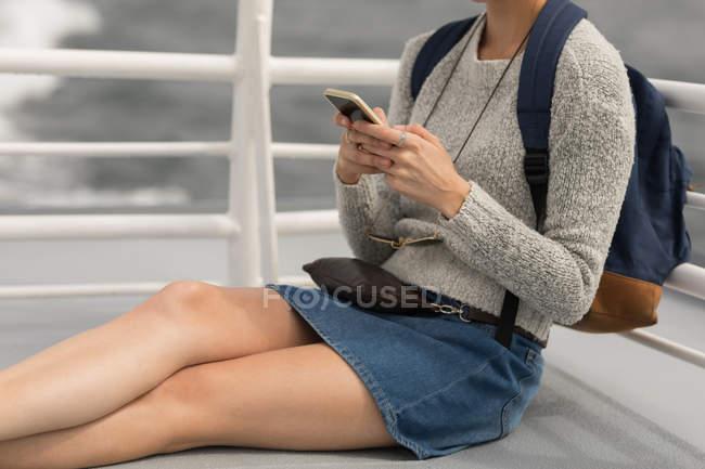 Розділ середині жінці за допомогою мобільного телефону на круїзному судні — стокове фото