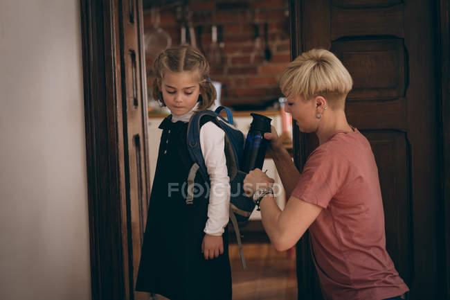 Mantenimiento de la madre la botella de agua en la mochila de la hija en casa - foto de stock