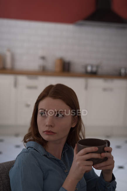 Thoughtful young woman holding a coffee mug at home — Stock Photo