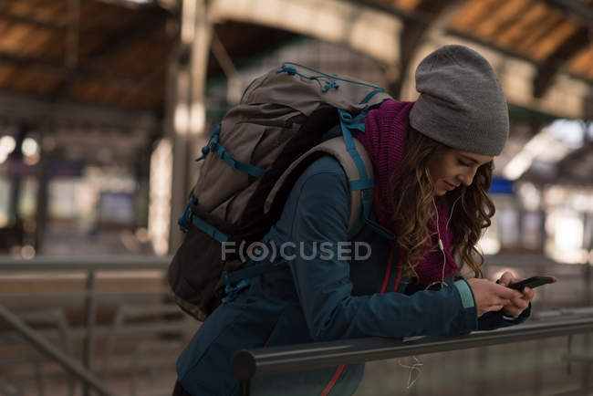 Young woman using mobile phone at railway station — Stock Photo