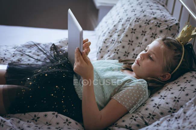 Девочка с цифровым планшетом на кровати в спальне — стоковое фото