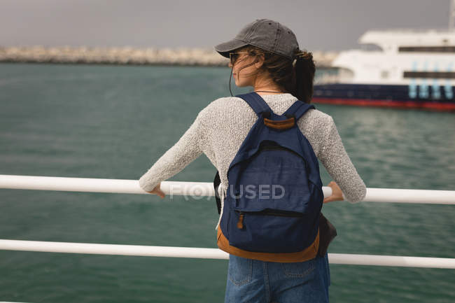 Rear view of woman with backpack standing on cruise ship — Stock Photo